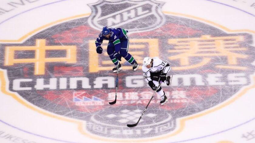 Brandon Sutter of the Vancouver Canucks skates against the Kings' Tyler Toffoli in Beijing.