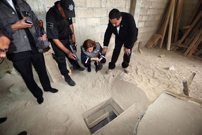 """In this photo provided by Mexico's attorney general, authorities inspect the exit of the tunnel they claim was used by drug lord Joaquin """"El Chapo"""" Guzman to break out of the Altiplano maximum security prison in Almoloya, west of Mexico City, Sunday, July 12, 2015. (Mexico's Attorney General's Office via AP)"""