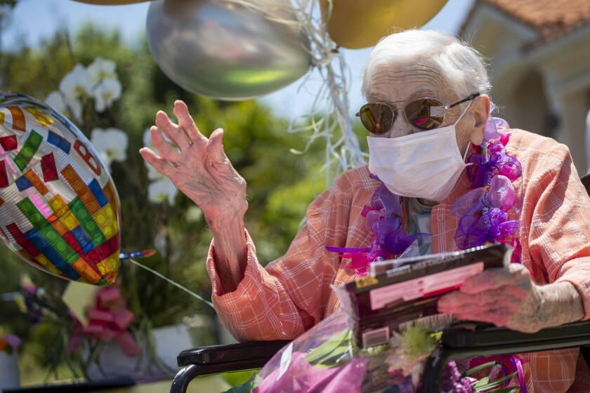 Mildred Stratton waves to a caravan of cars led by the Alhambra police and fire departments parading past her home, celebrating her 102nd birthday on May 20 in Alhambra.