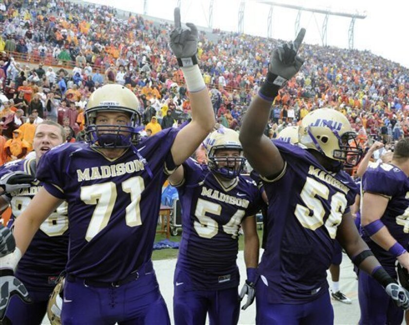 James Madison players, from left, Josh Wells, Chad Byers, and Jordon Stanton celebrate after defeating 13th ranked Virginia Tech 21-16 in a NCAA football game at Lane Stadium in Blacksburg, Va., Saturday, Sept. 11, 2010. (AP Photo/Don Petersen)