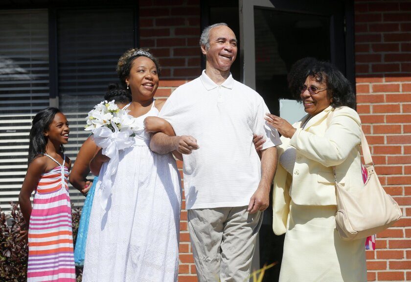 Miriam Reeves is escorted down the aisle by her father  Bernard Reeves, 64, who has Alzheimer's, and her mother Marie Reeves, right, during the Reeves / Davis wedding at Foundation Park Alzheimer's Care in Toledo, Ohio, Saturday, Aug. 16, 2014. Reeves wanted the ceremony to take place beneath the g