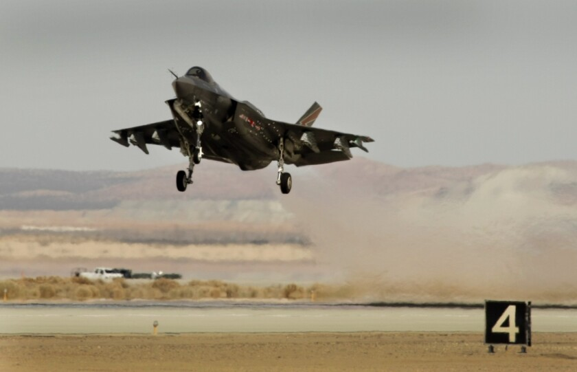 Lockheed Martin is cutting 4,000 positions and closing some plants due to reduced government defense spending, the firm said Thursday. Above, Lockheed Martin's F-35 Lightning II fighter jet during testing at Edwards Air Force Base in March.