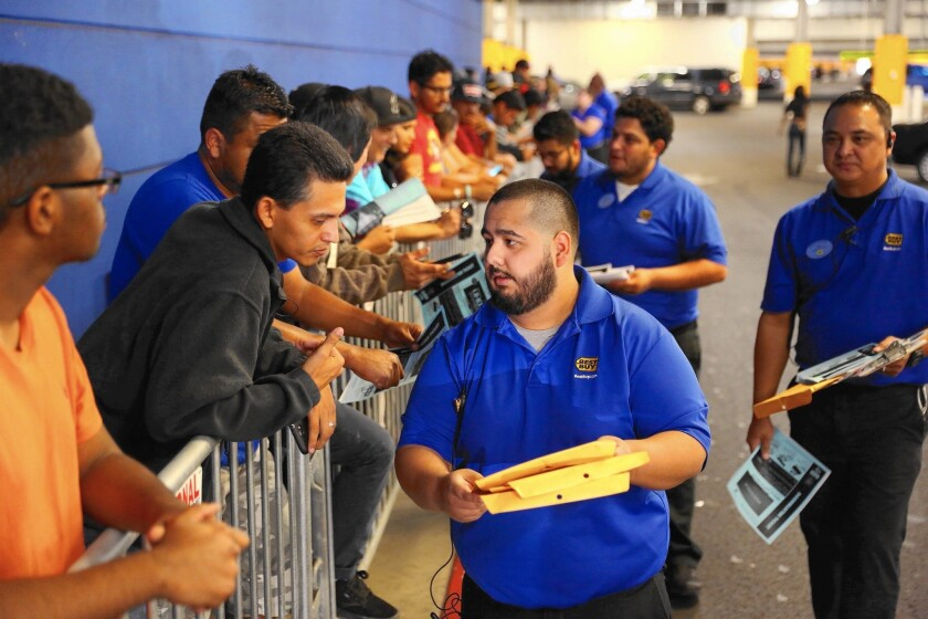 Projections show that more than 70% of total job openings through 2018 will be in occupations that require no college degree, including those in retail. Above, employees of a Best Buy store in Culver City hand out coupons to shoppers waiting in line on Thanksgiving.