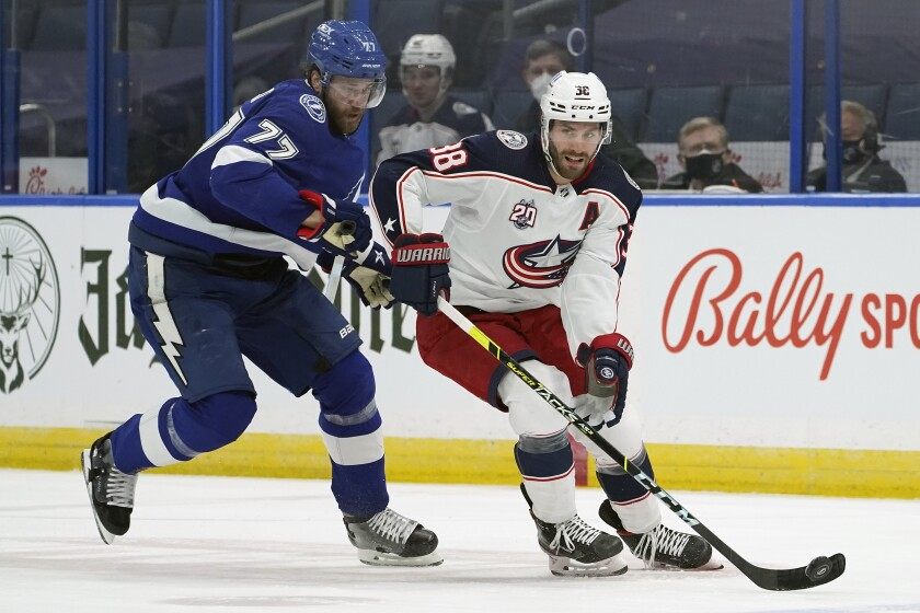 Columbus Blue Jackets center Boone Jenner (38) breaks out ahead of Tampa Bay Lightning defenseman Victor Hedman (77) during the first period of an NHL hockey game Thursday, April 1, 2021, in Tampa, Fla. (AP Photo/Chris O'Meara)