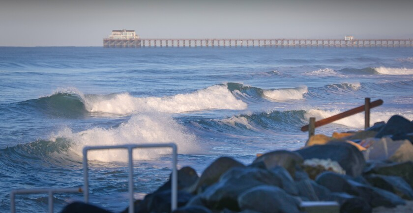 With the Oceanside Pier in the background, waves head for the shore as seen from Buccaneer Beach in Oceanside