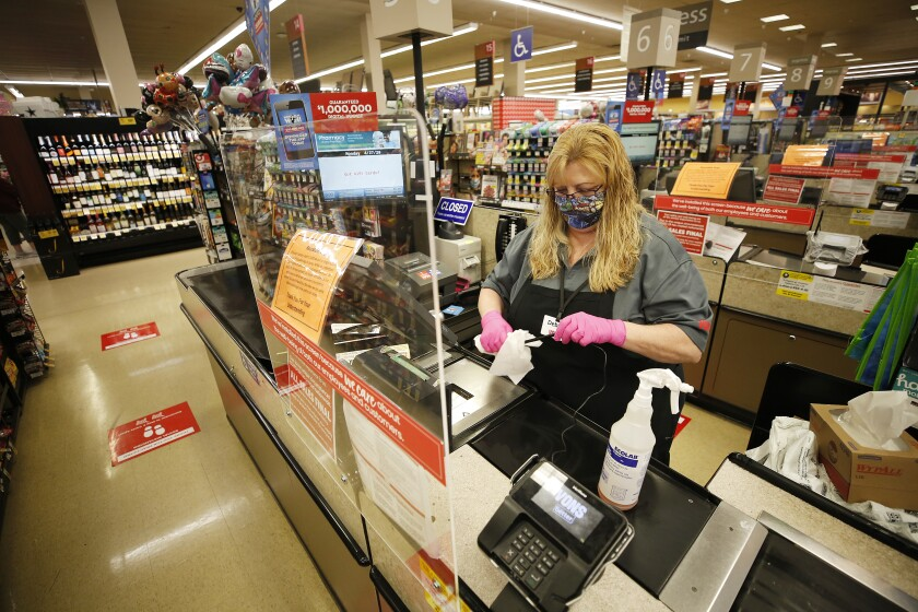 A Vons employee sanitizes equipment in a supermarket checkout line.