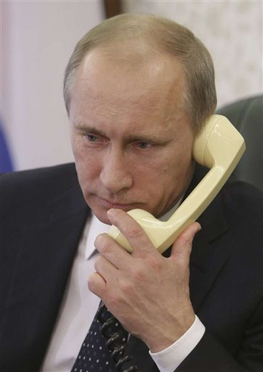 Russian Prime Minister Vladimir Putin talks on the phone with captains of the ships trapped in ice of the Sea of Okhotsk, in Moscow, Russia, Tuesday, Jan. 4, 2011. Two Russian icebreakers are trying to free a fishing trawler that among five ships with a total of more than 500 people aboard caught in heavy ice in the Sea of Okhotsk. (AP Photo / RIA Novosti, Alexei Nikolsky, Pool)