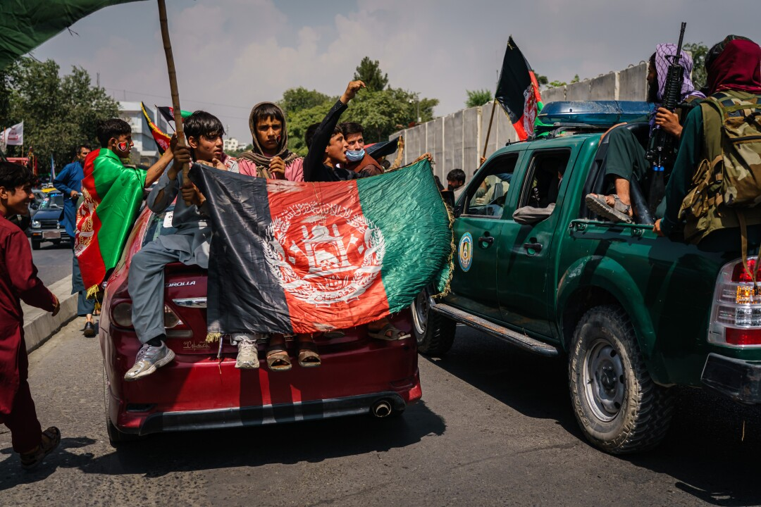 Afghans march down the street carrying banners and the flag of Afghanistan