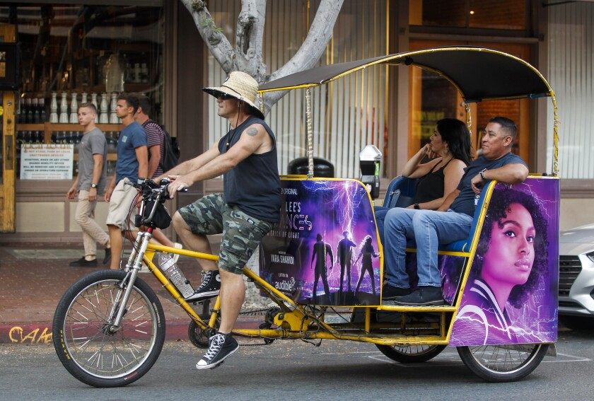 Pedicab driver Bill Fischer, who has been a pedicab driver for 21 years, takes a couple north on Fifth Avenue in Gaslamp Quarter on Tuesday, July 23, 2019 in San Diego, California.