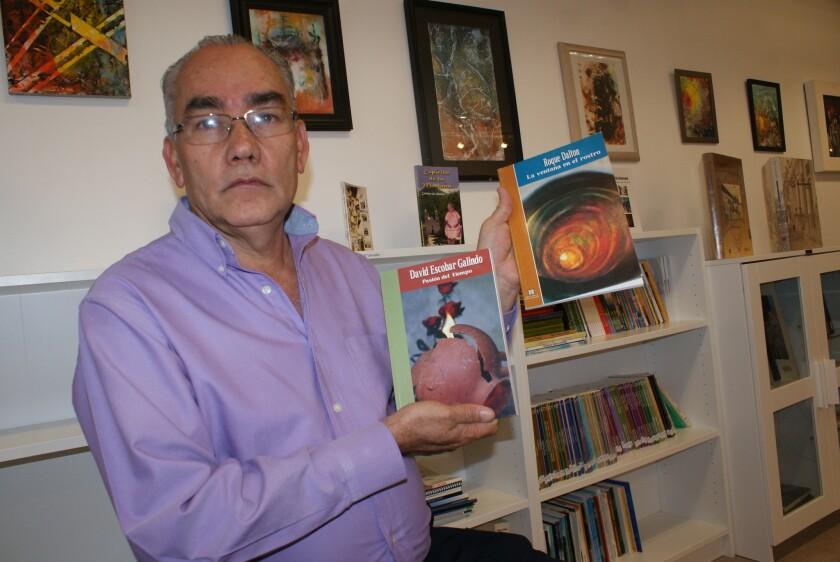 Jesús Aguilar muestra los libros de los escritores Roque Dalton y David Escobar Galindo, obras que se pueden encontrar en la Biblioteca Prudencia Ayala.
