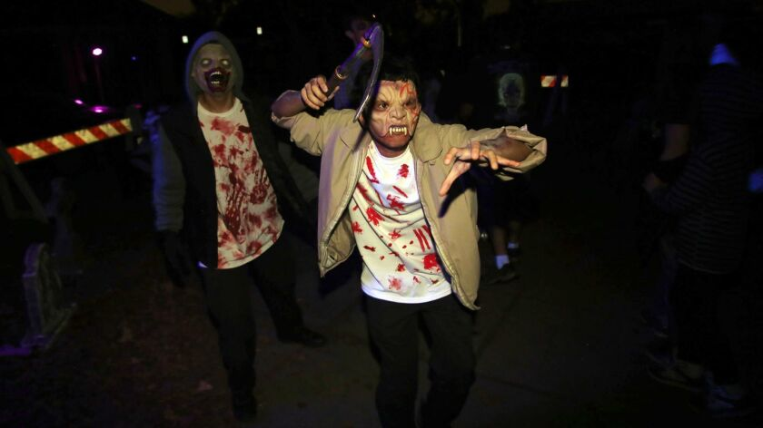 Volunteers from Burbank's Park and Recreation dressed as classic characters from horror movies jump