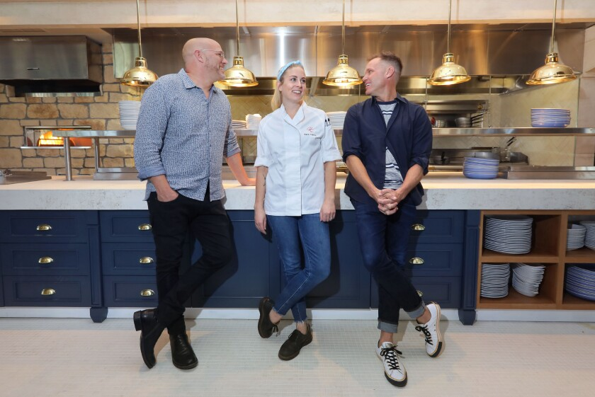 Herb & Sea Restaurant's co-owners Chris Puffer, left, and Brian Malarkey, right, with executive chef Sara Harris in front of the new Encinitas restaurant's exhibition kitchen in the main dining room.