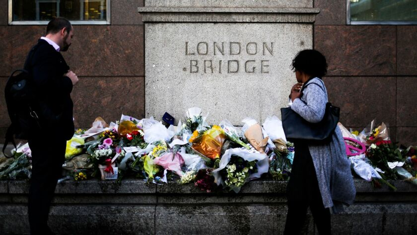 On Tuesday, passersby survey the floral tributes placed at London Bridge in honor of the victims of Saturday's attack.