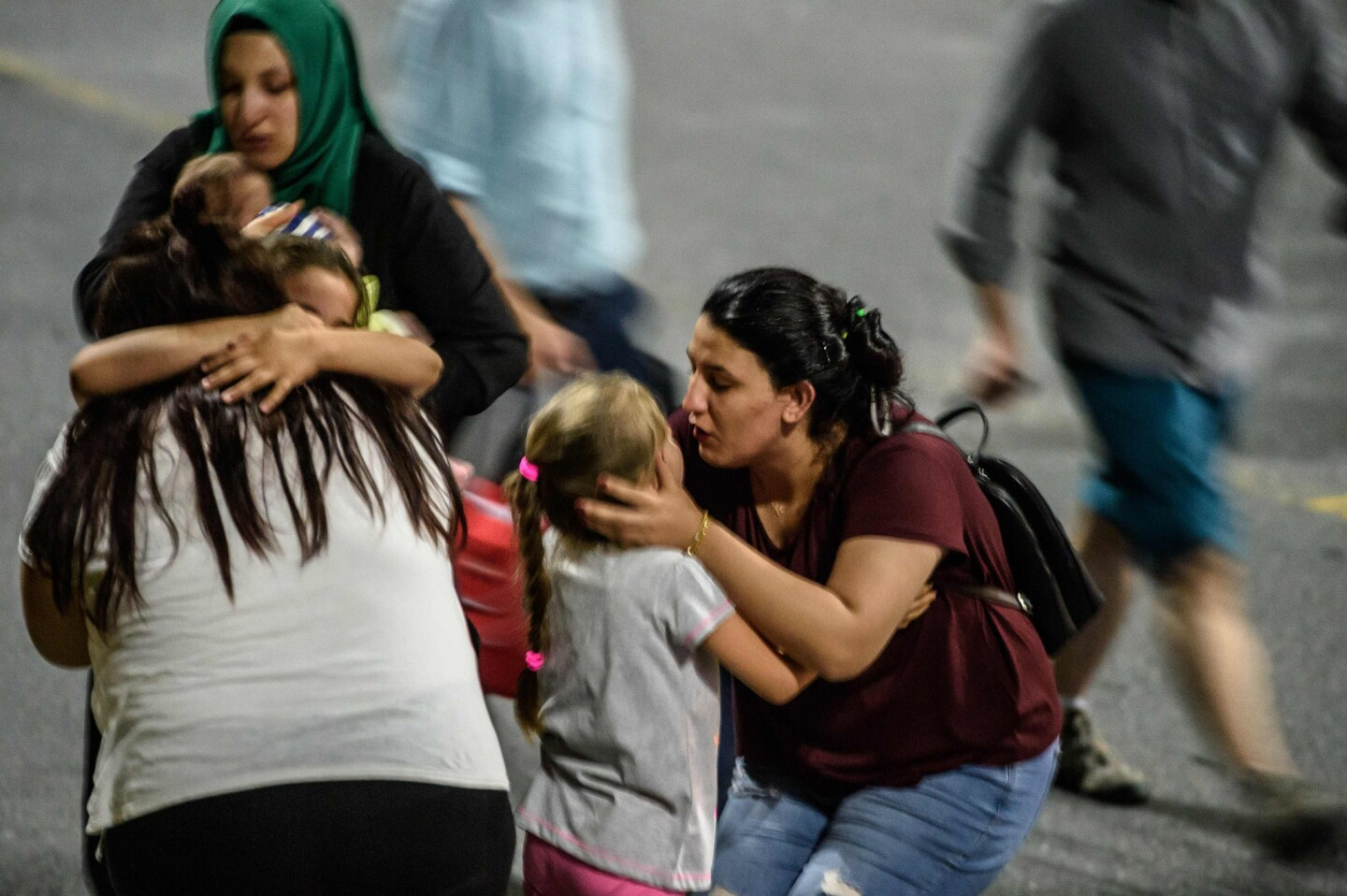 Children and their relatives embrace as they leave Ataturk airport in Istanbul.