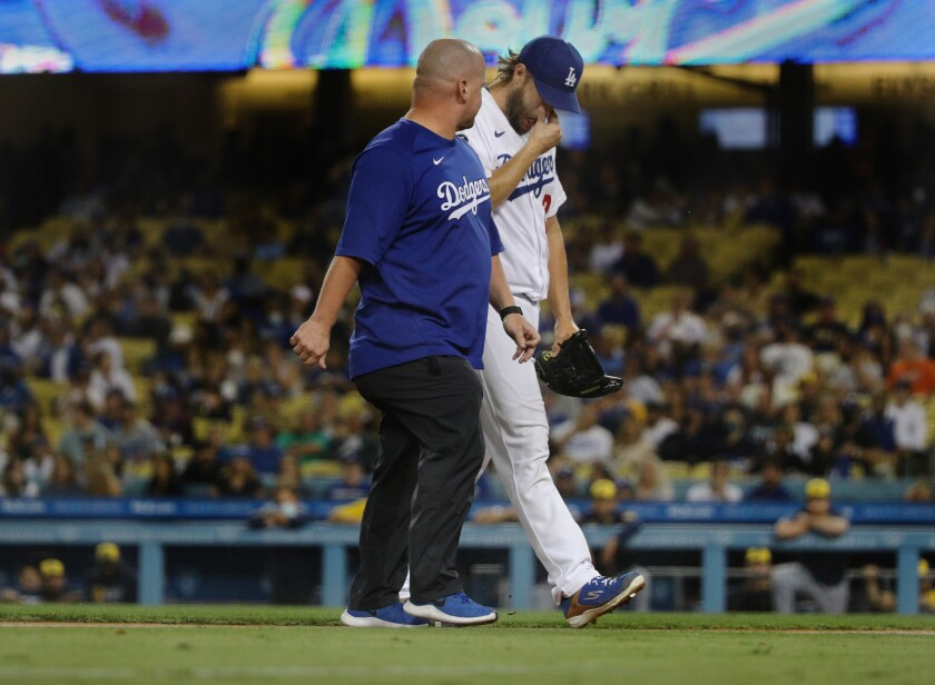 Clayton Kershaw walks off the mound with trainer Neil Rampe  on Friday night.