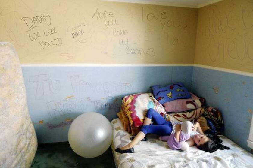 Mirka Moctezuma rests in the bedroom she shares with her three sisters in Painesville, Ohio, in June. Mirka was home with her father when immigration agents came to arrest him and deport him to Mexico last year. The four girls, who are American citizens, wrote messages on the walls of their room when their father was in an ICE detention facility before being deported. They live with their mother, Esperanza Pacheco, an illegal immigrant who was granted a stay of deportation that expires this month.