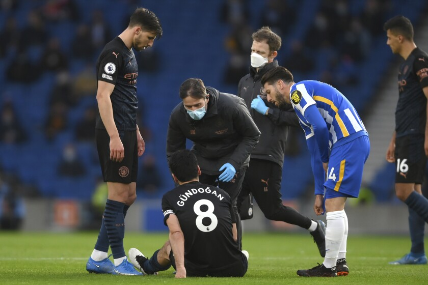 Manchester City's Ilkay Gundogan sits on the pitch after an injury during the English Premier League soccer match between Brighton & Hove Albion and Manchester City at the Amex stadium in Brighton, England, Tuesday, May 18, 2021. (Mike Hewitt, Pool via AP)