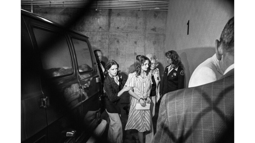 Patty Hearst, shown in handcuffs, is escorted by two women near the inmate entrance of the criminal court building in Los Angeles, on May 28, 1976.