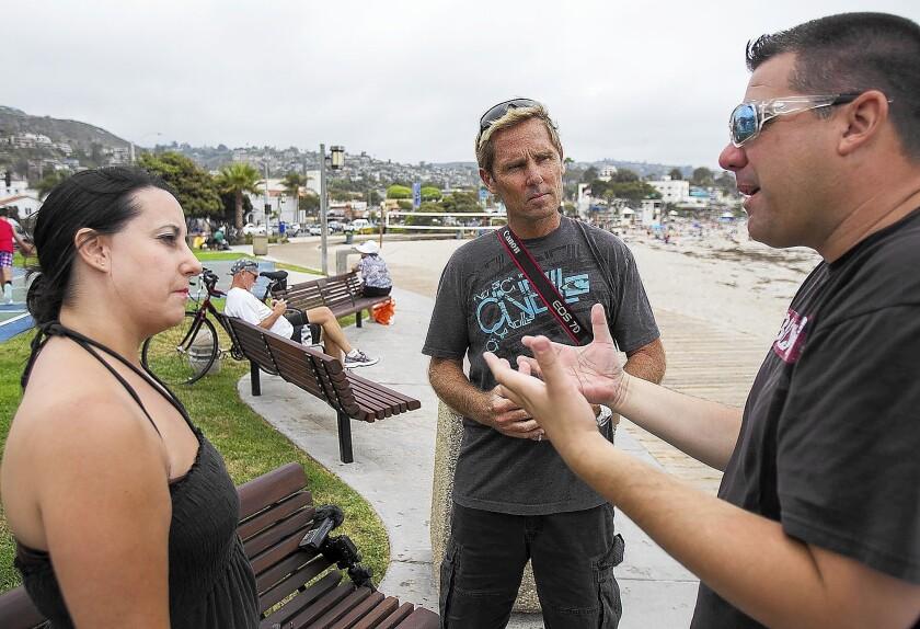 David Makela, center, owner of Vizual Living, interviews Dustin and Katrina Powell of Tucson, Ariz., at Main Beach in Laguna Beach on Monday.