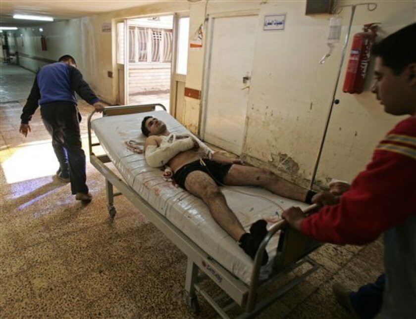 A man injured in a twin bombing near the entrance to a police academy is transported out of the emergency room at a hospital in Baghdad, Iraq, Monday, Dec. 1, 2008. At least 16 people were killed and 46 wounded in a nearly simultaneous double bombing near a police academy in eastern Baghdad. A suicide attacker detonated his explosives vest packed with ball-bearings at the entrance to the academy, then a car bomb exploded about 150 yards (137 meters) away, apparently aimed at those responding to the initial blast, the U.S. military said. (AP Photo/Karim Kadim)