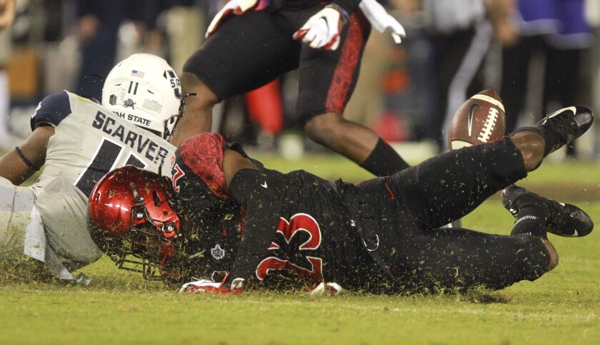 San Diego State cornerback Darren Hall grinds through the grass during a play in last season's game against Utah State.