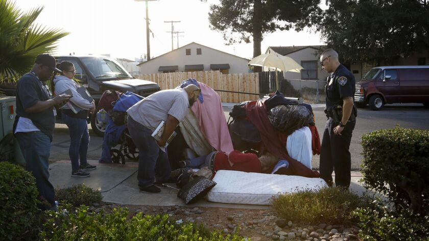 Jonathan Alatorre from Vista Hill makes contact with a man homeless man who was sleeping on the side
