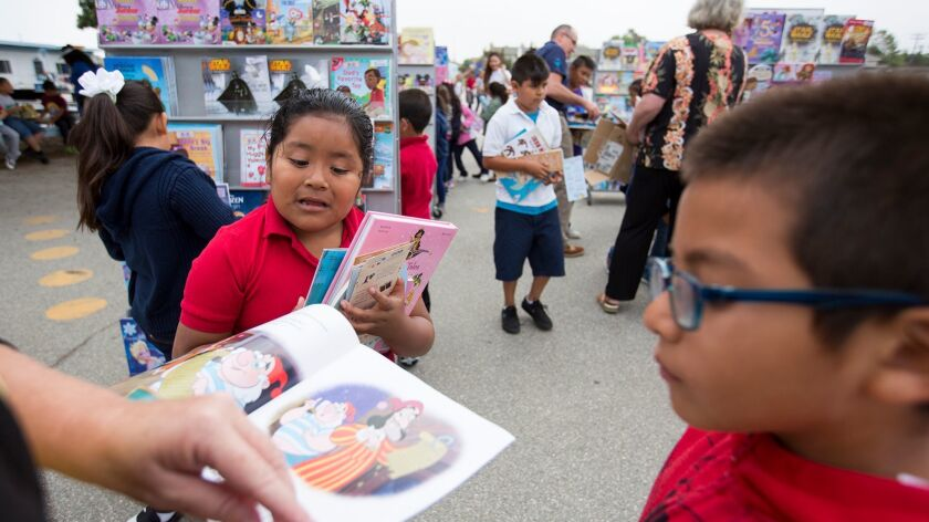 Whittier Elementary School students Sandra Correa Martinez and Yvan Tapia look at one of the thousan