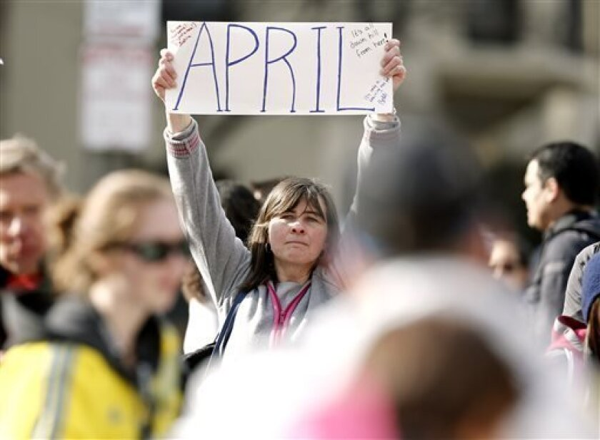 Justine Franco of Montpelier, Vt., holds up a sign near Copley Square in Boston looking for her missing friend, April, who was running in her first Boston Marathon Monday, April 15, 2013. Two bombs exploded near the finish line of the marathon on Monday, killing at least two people and injuring at