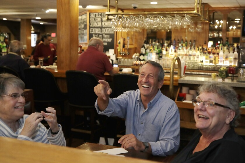 Republican presidential candidate, former South Carolina Gov. Mark Sanford chats with patrons at the Puritan Backroom restaurant, as he campaigns, Thursday, Sept. 19, 2019, in Manchester, N.H. (AP Photo/Elise Amendola)