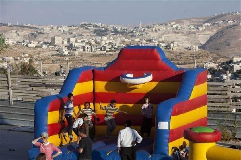 Israeli children play near a construction site during a ceremony to mark the resumption of the construction of housing units in an east Jerusalem neighborhood, Sunday, Aug. 11, 2013. Israel's housing minister on Sunday gave final approval to build nearly 1,200 apartments in Jewish settlements, just three days before Israeli-Palestinian peace talks are to resume in Jerusalem. (AP Photo/Sebastian Scheiner)
