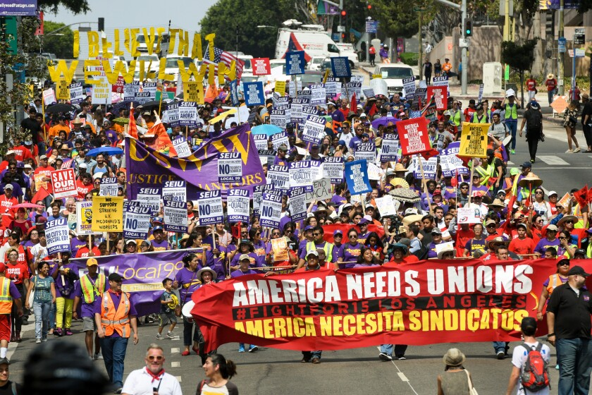 Demonstrators march through downtown Los Angeles during a Labor Day protest organized by the SEIU in