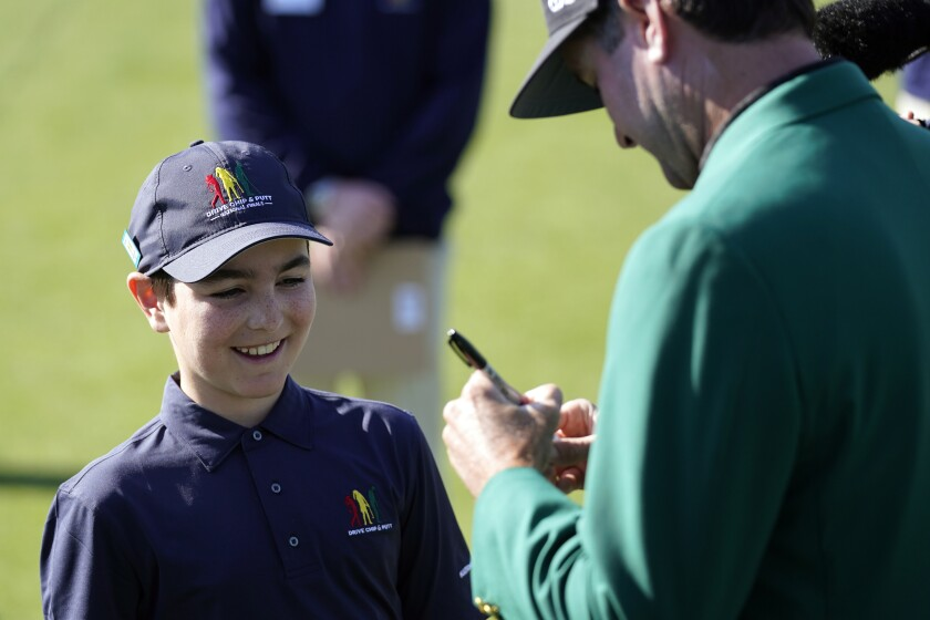 Lucas Bernstein, left, waits as Masters Champion Bubba Watson signs a golf ball for him during the Drive Chip & Putt National Finals at Augusta National Golf Club, Sunday, April 4, 2021, in Augusta, Ga. (AP Photo/David J. Phillip)
