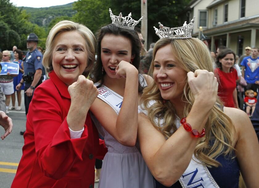 La candidata presidencial Hillary Rodham Clinton, flexiona sus músculos junto con Miss Teen New Hampshire, Allie Knault, al centro, y Miss New Hampshire, Holly Blanchard,durante un desfile del 4 de Julio en Gorham, Nueva Hampshire el 4 de julio de 2015. (Foto AP/Robert F. Bukaty)
