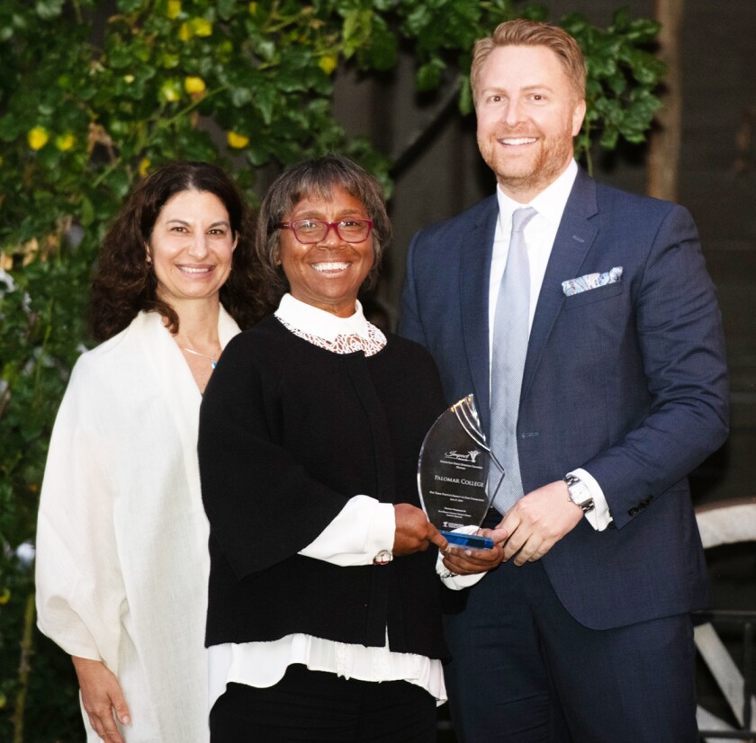Dr. Joi Lin Blake, center, accepting an Impact Award for Palomar College from presenters Anette Blatt of Scripps Health and Nathan Schmidt of San Diego County Credit Union.