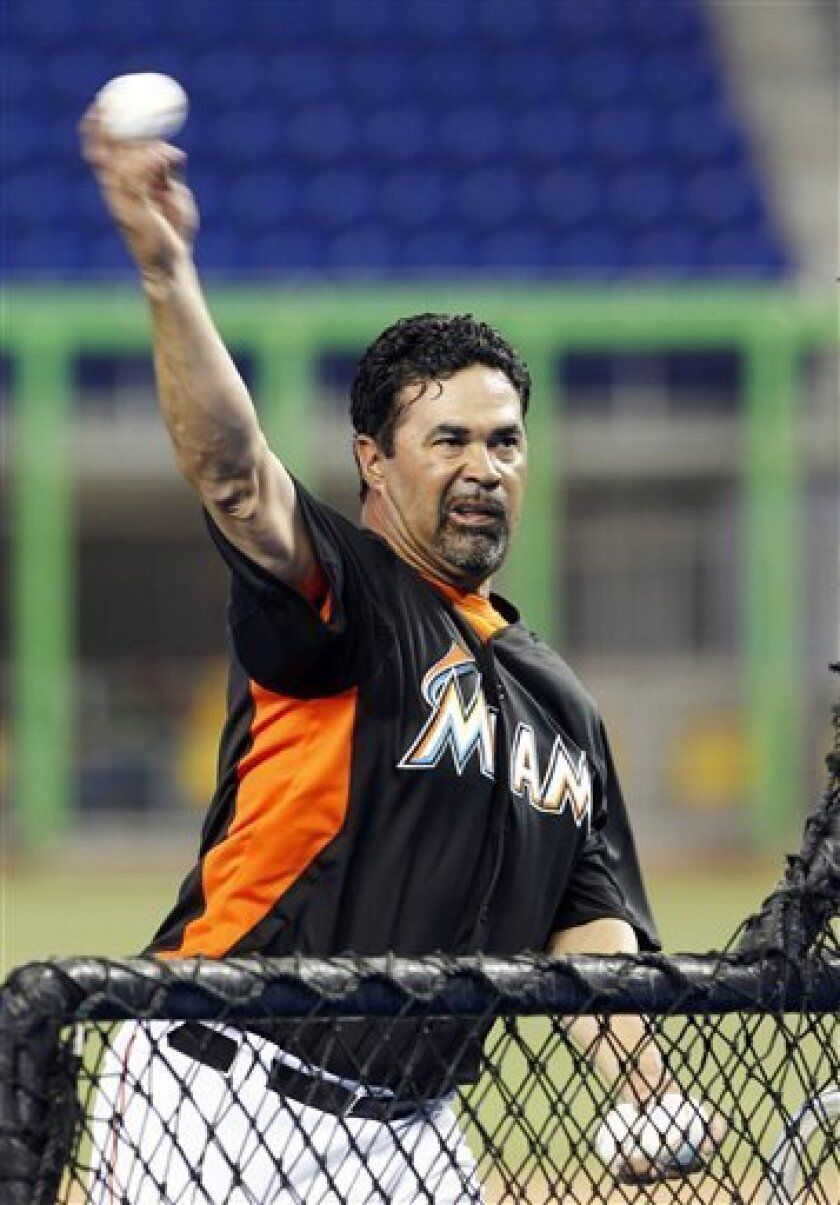 Miami Marlins manager Ozzie Guillen pitches during batting practice before a spring training baseball game against the New York Yankees in Miami, Monday, April 2, 2012. (AP Photo/Wilfredo Lee)