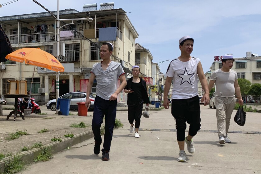 In this June 5, 2019, photo, residents of the Hui Muslim ethnic minority walk in a neighborhood near an OFILM factory in Nanchang in eastern China's Jiangxi province. The Associated Press has found that OFILM, a supplier of major multinational companies, employs Uighurs, an ethnic Turkic minority, under highly restrictive conditions, including not letting them leave the factory compound without a chaperone, worship, or wear headscarves. (AP Photo/Ng Han Guan)