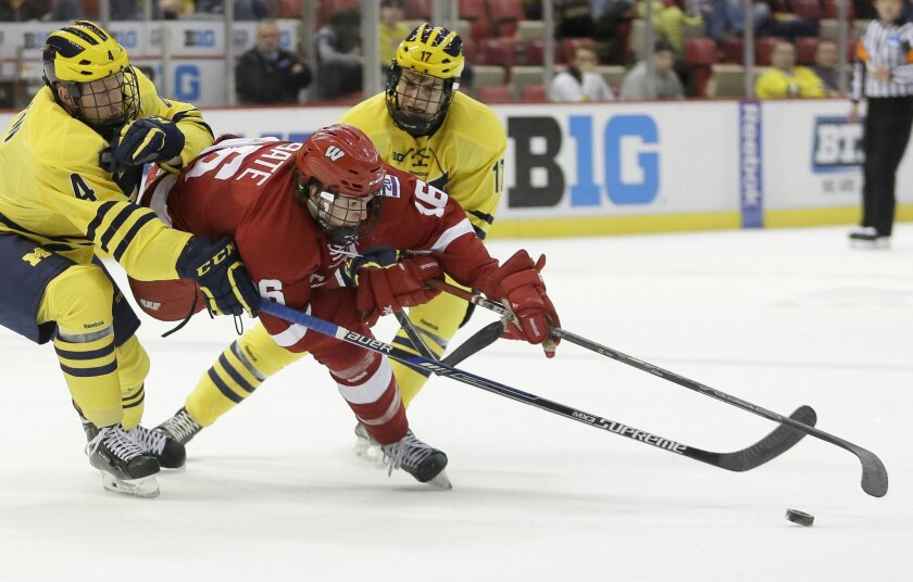 FILE - In this March 19, 2015, file photo, Michigan's Cutler Martin (4) and Tony Calderone (17) try to steal the puck from Wisconsin's Joseph LaBate (16) during the second period of an NCAA college hockey game in the Big Ten Conference tournament in Detroit. With the exposure provided by the Big Ten Network, an abundance of resources and strong traditions in the sport, the league was set up for success. Now in its third season, the league has not lived up to expectations. Officials are confident it will in time, and also believe the strength of the Big Ten brand will nudge a niche sport closer to the mainstream and spur expansion to other big-time schools. (AP Photo/Duane Burleson, File)