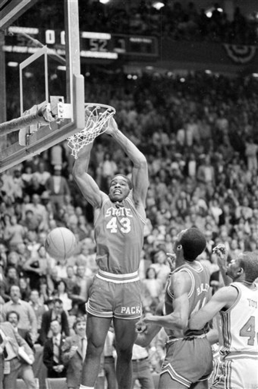FILE- This April 4, 1983 file photo shows North Carolina State's Lorenzo Charles (43) dunking the ball in the basket to give N.C. State a 54-52 win over Houston in the NCAA Championship game in Albuquerque, N.M. A tour bus official says the former North Carolina State basketball star , was killed when a bus he was driving crashed in Raleigh. Charles was 47. (AP Photo/File)