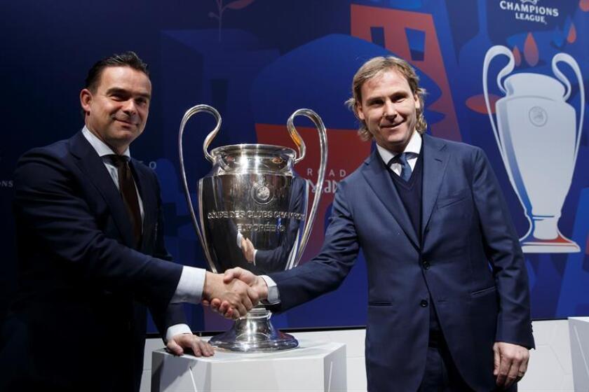 El director deportivo del Ájax de Ámsterdam, Marc Overmars (i), y el vicepresidente del Juventus Turín, Pavel Nedved, se saludan delante del trofeo de la Liga de Campeones de la UEFA durante el sorteo de cuartos de final de la Liga de Campeones celebrado este viernes en la sede de la UEFA en Nyon, Suiza. EFE