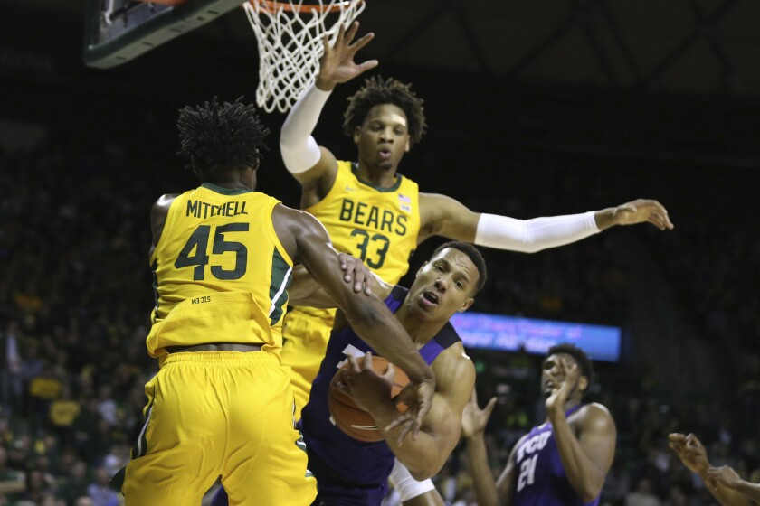 TCU guard Desmond Bane, right, grabs the arms of Baylor guard Davion Mitchell, left, while being pressured by forward Freddie Gillespie, in the first half of an NCAA college basketball game, Saturday, Feb. 1, 2020, in Waco, Texas. (AP Photo/Rod Aydelotte)