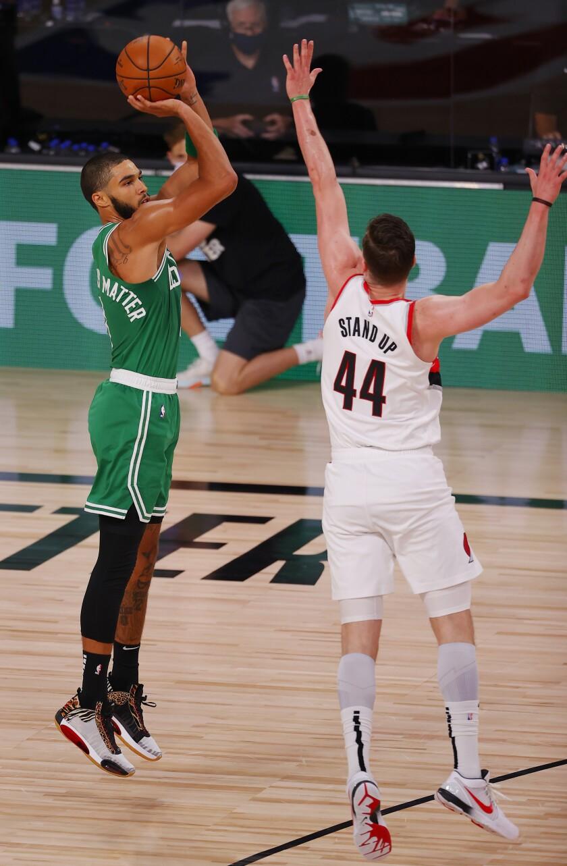 Boston Celtics' Jayson Tatum (0) shoots against Portland Trail Blazers' Mario Hezonja (44) during an NBA basketball game Sunday, Aug. 2, 2020, in Lake Buena Vista, Fla. (Mike Ehrmann/Pool Photo via AP)