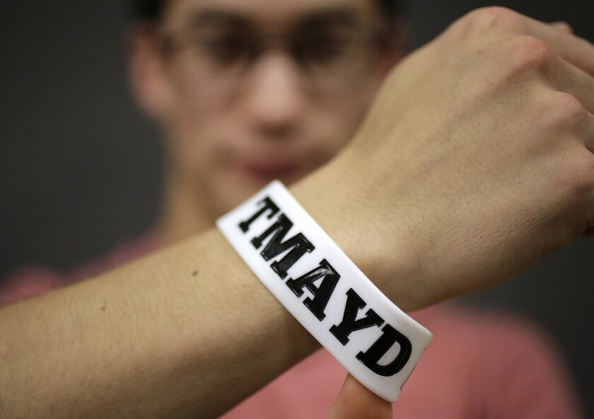 """In this Monday, Feb. 1, 2016 photo, Massachusetts Institute of Technology student Andy Trattner, of Portland, Ore., displays a wrist band that features the acronym TMAYD for """"Tell Me About Your Day,"""" a campaign to encourage students to talk to one another in an effort to defuse to the stress of cam"""
