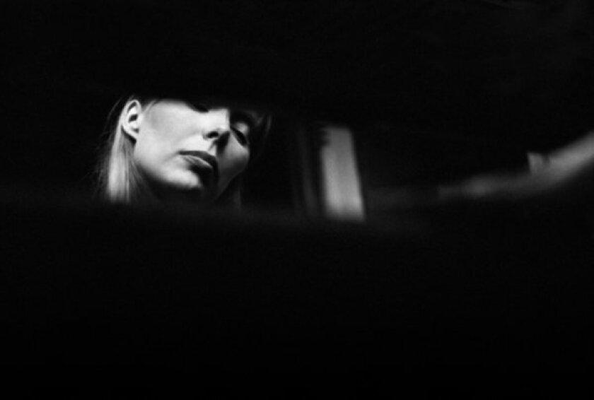 Joni Mitchell sitting at a piano, taken by Graham Nash.