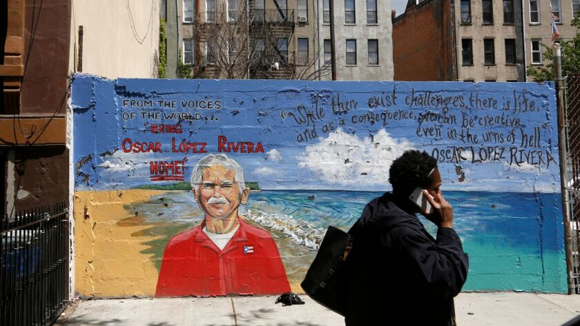 A pedestrian walks past a mural of Oscar Lopez Rivera in New York, Tuesday, May 9, 2017. (AP Photo/S