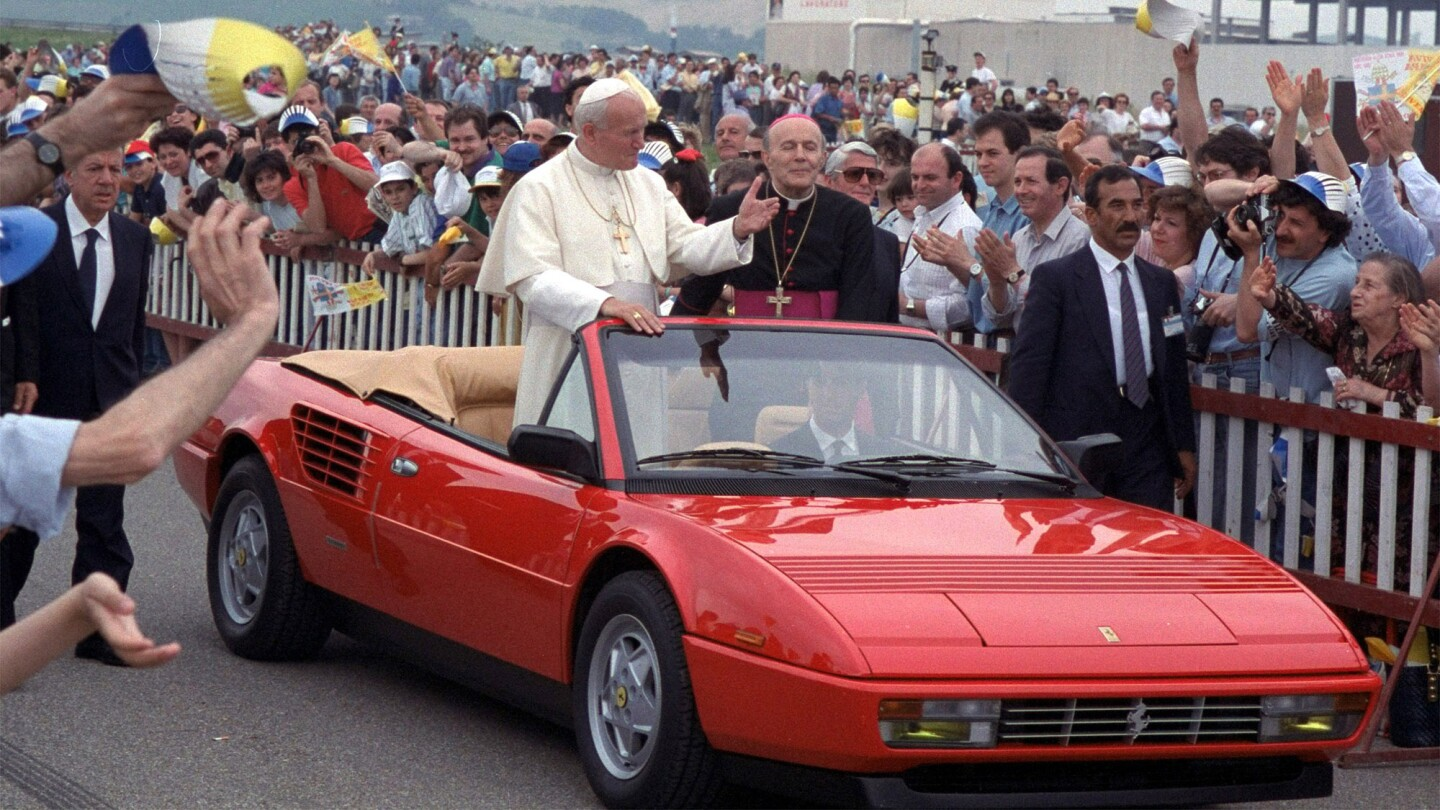 Pope John Paul II rides in a brand-new Ferrari Mondial Cabriolet as he visits a Ferrari manufacturer in Fiorano, Italy, on June 4, 1988.