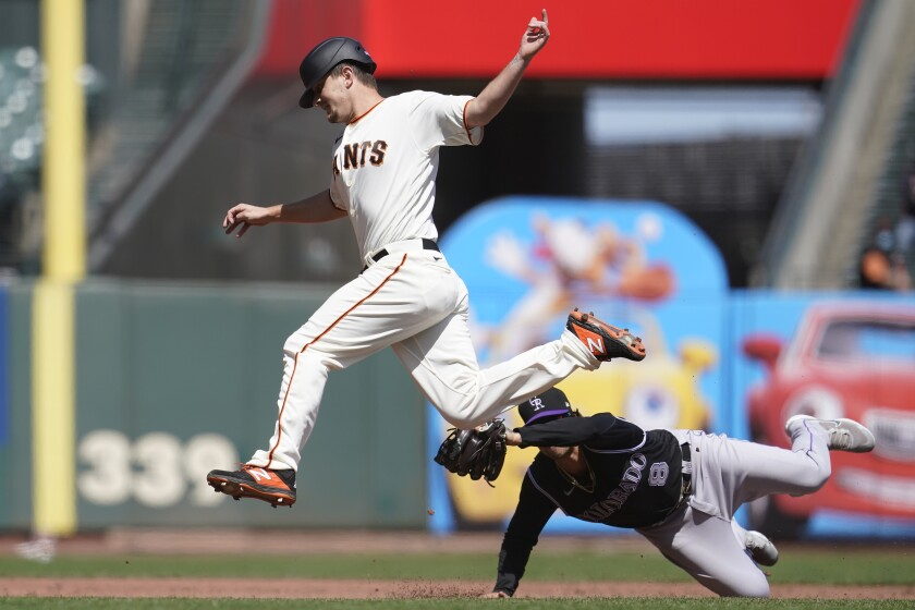 San Francisco Giants' Alex Dickerson, top, is tagged out by Colorado Rockies third baseman Josh Fuentes while trying to advance to third base during the third inning of a baseball game in San Francisco, Saturday, April 10, 2021. (AP Photo/Jeff Chiu)