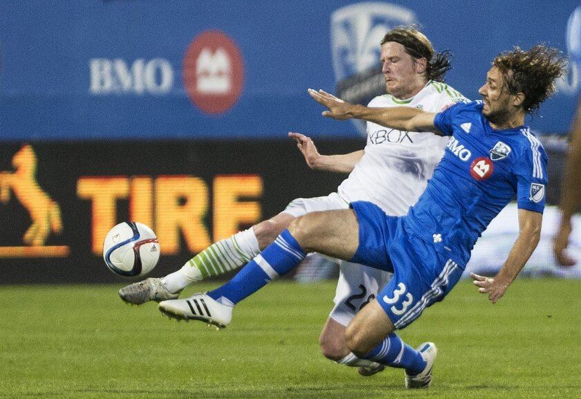 Montreal Impact's Maro Donadel, right, challenges Seattle Sounders' Erik Friberg during the first half of an MLS soccer game in Montreal, Saturday, July 25, 2015. (Graham Hughes/The Canadian Press via AP)