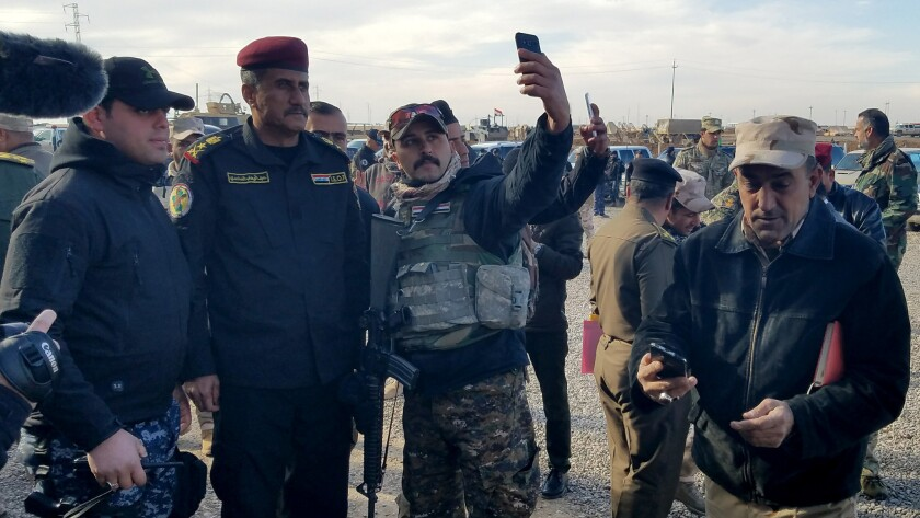 Lt. Gen. Abdel Wahab Saadi, Iraqi Special Forces commander, center, does not have a Facebook account but has posed for enough selfies that troops recognize him - and request more.