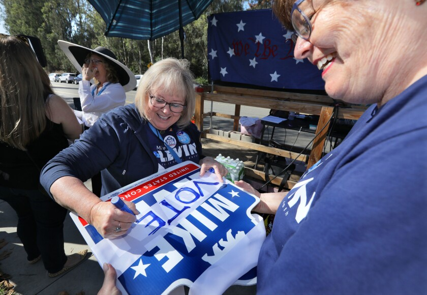 Peggy Ancinec adds a message to a Mike Levin campaign sign before a Levin campaign rally in 2018. Rallies, precinct walking and other traditional forms of campaigning are being sidelined due to the coronavirus pandemic.