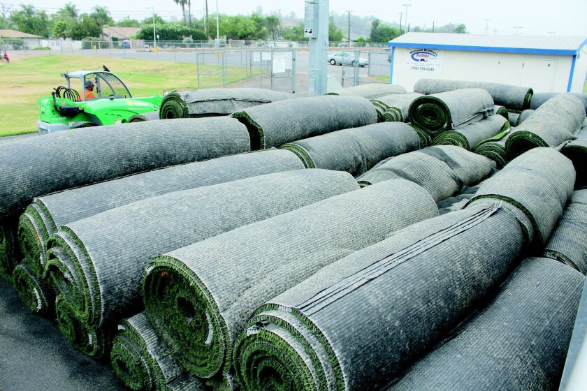 Rolls of old turf from Bulldog Stadium are piled next to the home-team bleachers.